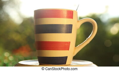 striped cup with coffee on rotated plate