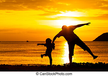 Father and son playing on the beach at the sunset time
