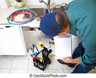 Plumber on the kitchen - Plumber with Plumbing tools on the...