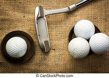 Golfballs - Golf balls lying on metal plates next to a...