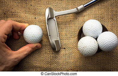 Putter and golfballs - A hand holding a golf ball near a...