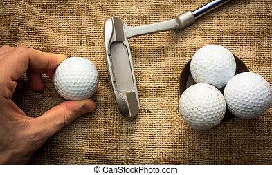 Putter and golfballs - A hand holding a golf ball near a...