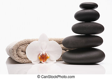 spa stones towel and orchid on white background