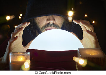 Crystal Ball - Very low key portrait of hooded man with eyes...