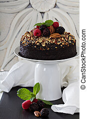 Chocolate banana cake with nuts decorated with berries