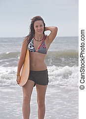 Athletic teen girl smiling with skimboard - Smiling athletic...