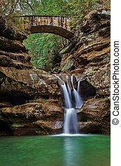 Waterfall Serenity - Serene waterfall with stone footbridge...