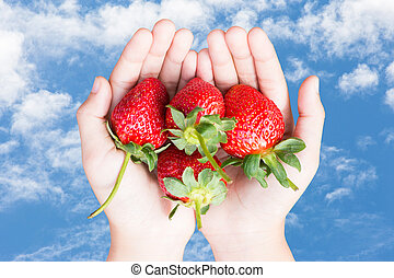 Clound in blue sky - hands holding strawberries over clound...