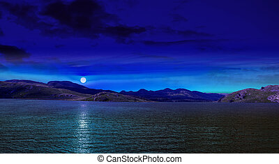 Moon reflected on the water - Night scene in mountain with..