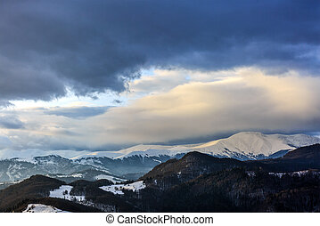 Landscape with snowy mountains under cloudy sky