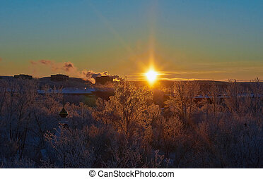 Beautiful sunrise over the snow-covered winter town.
