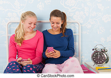 Teen girls with smartphones - Teen girls in pyjama sitting...