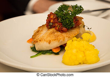 Broiled Fish Garnished with Salsa and Kale - A serving of...