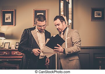 Tailor and client choosing cloth for custom made suit
