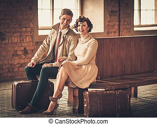 Vintage style young couple with suitcases on a train station