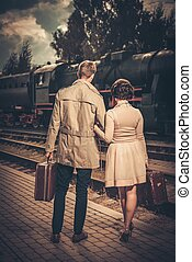 Vintage style couple with suitcases on train station...