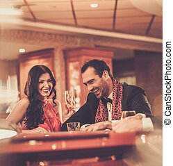 Couple behind poker table in a casino
