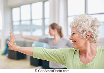 Senior woman doing stretching exercise at yoga class -...