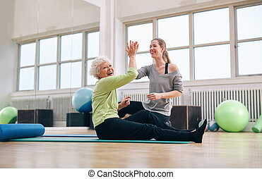 Senior woman rejoicing health success with her instructor -...