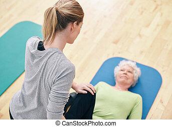 Female coach helping senior woman exercising in gym