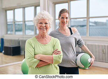 Senior woman at health club with gym instructor