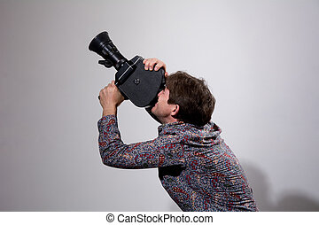 A man with an old movie camera on a gray background...