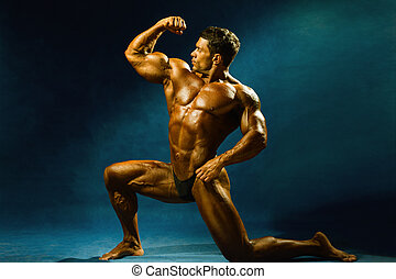 Strong muscular man bodybuilder shows his muscles Sportsman...