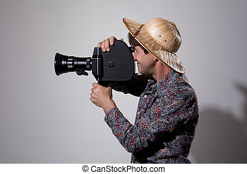 A man in a straw hat with an old movie camera on a gray...