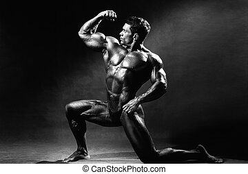 Strong muscular man bodybuilder shows his muscles. Sportsman...