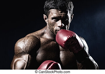 Strong muscular boxer in red boxing gloves A man in a boxing...