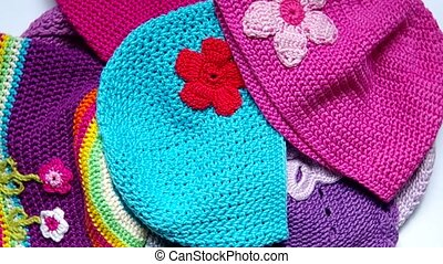 Girls colorful crocheted hats are rotates on the table