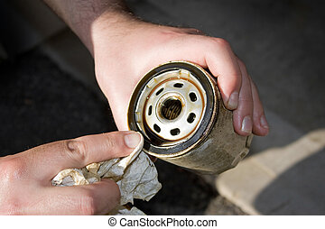 Dirty Used Oil Filter - A backyard mechanic wipes the seal...