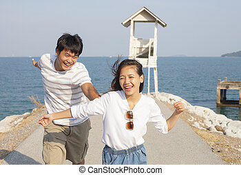 young man and pretty woman joyful emotion and playing at sea...