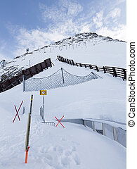 sign warning of the danger - high mountain with snow fences...