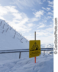 sign warning - high mountain with snow fences and yellow...