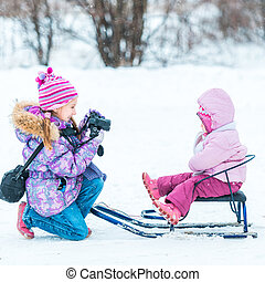 little girl photographed her sister sitting on a sled in the...