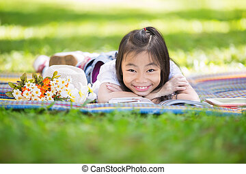 Funny little Asian girl reading and learning with tablet pc...