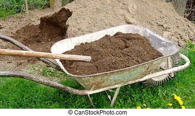 Takeaway soil in hand wheelbarrow in garden