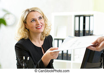 Smiling mature businesswoman giving paper to colleague