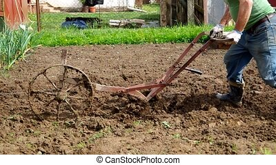 Electric winch and hand plow for pl - Plowing the soil with...
