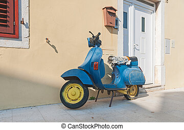 Old blue scooter parked by the wall in the empty street.