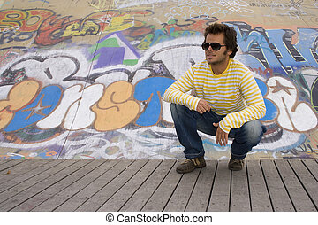 Urban Model - young men next to a graffiti wall, showing the...