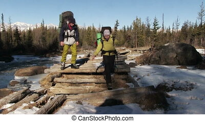 Old Wood Bridge - Tourists with large backpacks pass through...