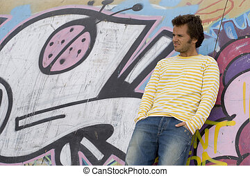 Urban style - young men next to a graffiti wall, showing the...