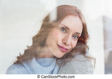 Pretty redhead in warm clothing seen through glass window