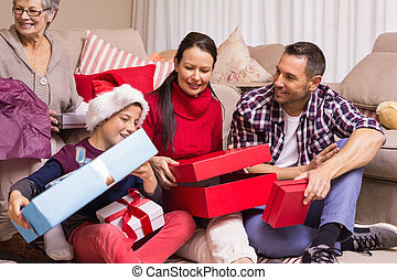 Happy family opening christmas gifts together