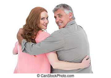 Casual couple standing arms around on white background