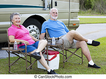 RV Seniors Relaxing Outdoors - Senior couple on vacation,...