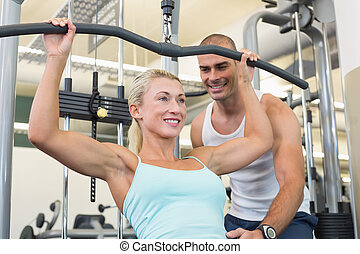 Male trainer assisting woman on a lat machine in gym
