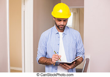 Casual architect reading his notes in a new house